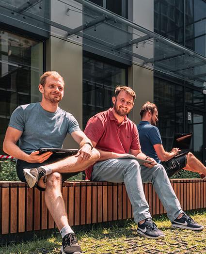 Trzech uśmiechniętych mężczyzn siedzi przez budynkiem na ławce. Na kolanach trzymają laptopy.