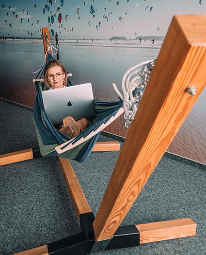 Kobieta siedzi na hamaku w biurze, na kolanach trzyma laptopa.
