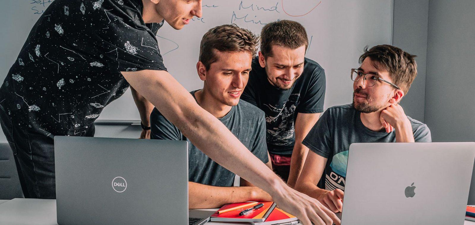 Czterech mężczyzn rozmawia przy biurku, dwoje z nich siedzi przed laptopami. Za nimi wisi na ścianie biała tablica.