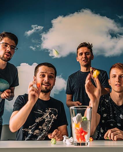 Czterech mężczyzn rzuca kuleczkami do szklanki na stole. Dwaj z nich siedzą przy blacie, pozostali stoją za nimi.