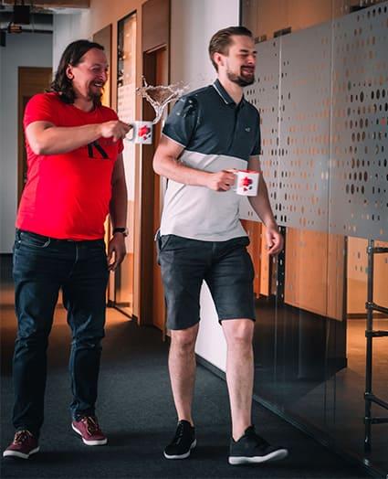 Dwaj uśmiechnięci mężczyźni idą korytarzem trzymając firmowe kubki. Jeden zostaje oblany wodą.