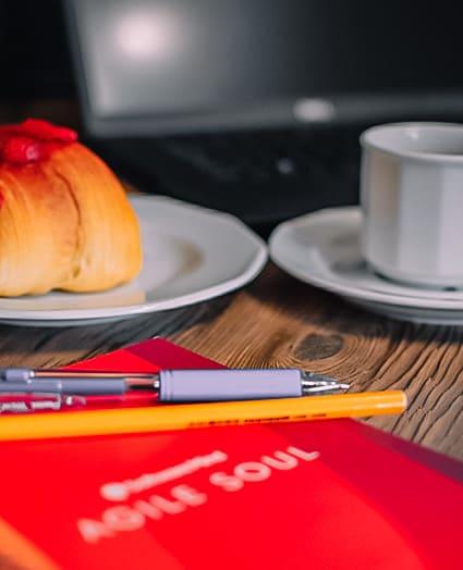 Bliskie ujęcie na biurko z firmowym notesem, długopisami, monitorem i kawą.