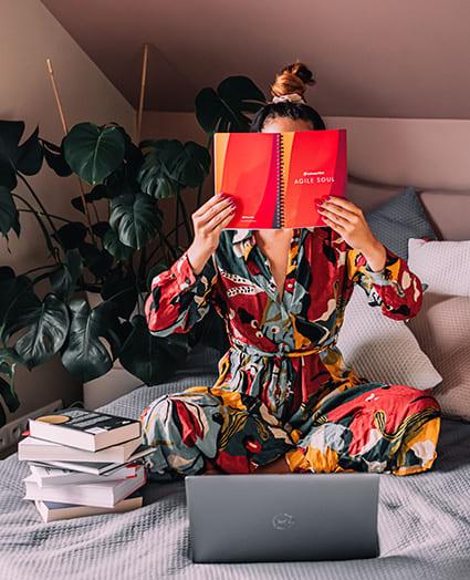 Kobieta siedzi na łóżku i zakrywa twarz firmowym notesem. Przed nią leży otwarty laptop i kilka książek ustawionych jedna na drugiej.