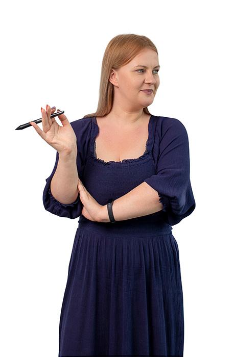 Laura stoi bokiem z założonymi rękoma. Jedną ma w połowie uniesioną i trzyma w niej długopis.