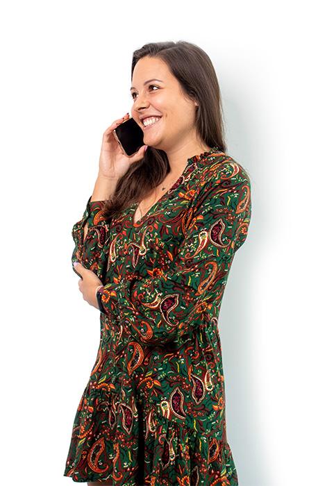 Uśmiechnięta Marta stoi bokiem i rozmawia przez telefon.