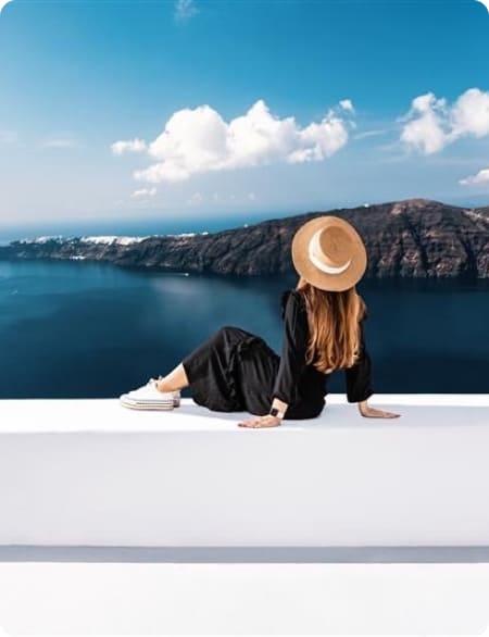 Kobieta siedzi z wyprostowanymi nogami na murku tyłem do obiektywu. Przed nią widok na morze i wzgórza.