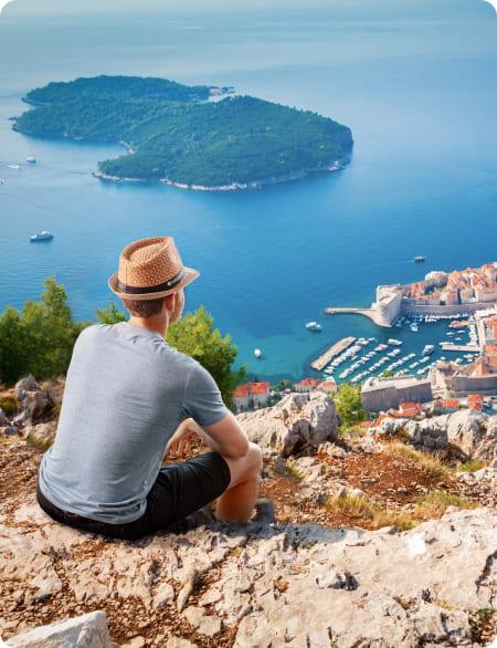 Mężczyzna siedzi na wzgórzu nad morzem, tyłem do obiektywu. Nosi kapelusz z logo Software Mind.