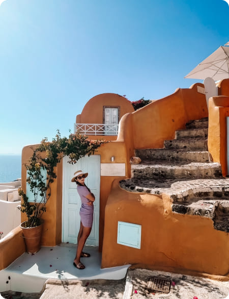 Kobieta w kapeluszu stoi na tle nadmorskich budynków w śródziemnomorskim stylu.